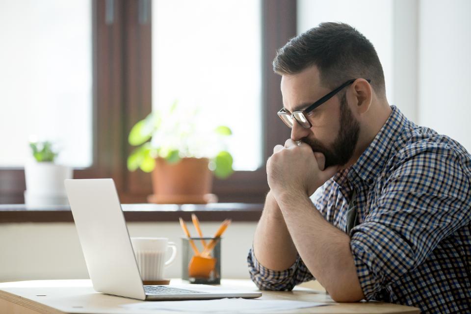 nervous man staring at laptop